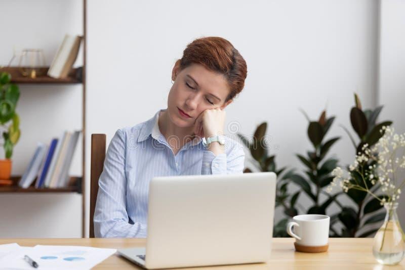 Пробуренная коммерсантка спать в наличии сидящ на столе офиса стоковое изображение rf