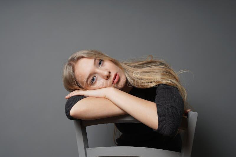 Пробуренная молодая женщина сидя верхом на на стуле с головой отдыхая на backrest стоковое изображение rf