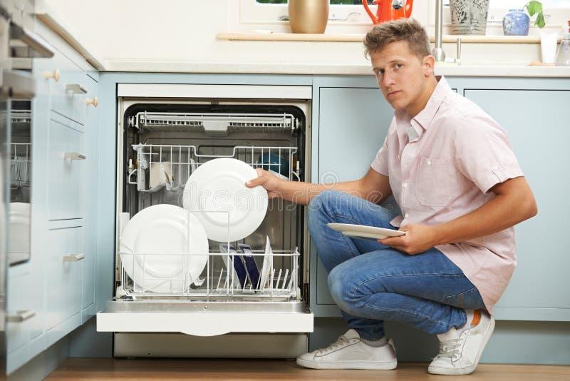 Пробуренная судомойка загрузки человека в кухне стоковое фото rf