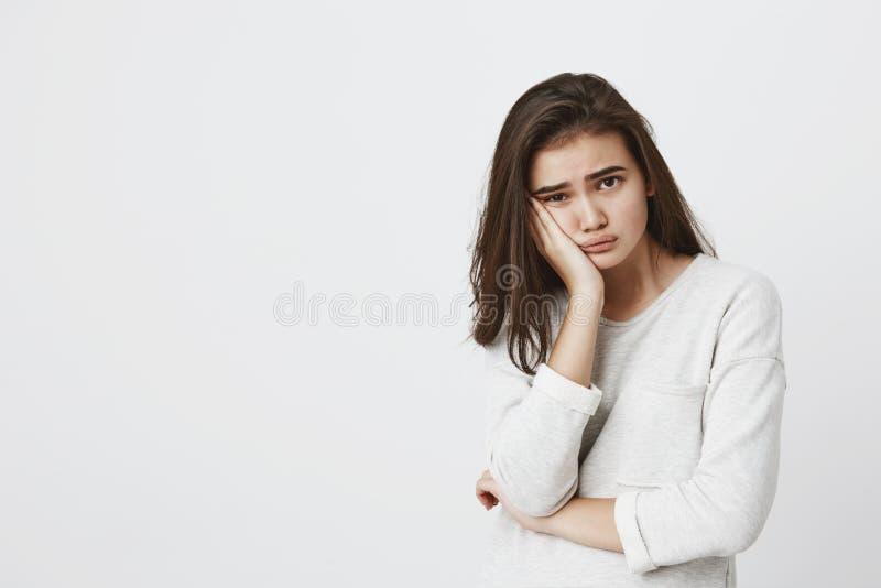 Пробуренная утомленная женщина youngbrunette нося ее темные волосы свободно, хмурящся сторона в неудовлетворенности, держа руку н стоковая фотография rf