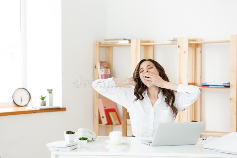 Пробуренные бизнесмены: женщина сидя на столе с закрытыми глазами и зевая Молодая кавказская бизнес-леди на ее офисе стоковое фото rf