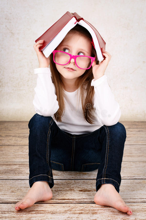 Пробуренные стекла маленькой школьницы нося и прятать в книге стоковые изображения rf