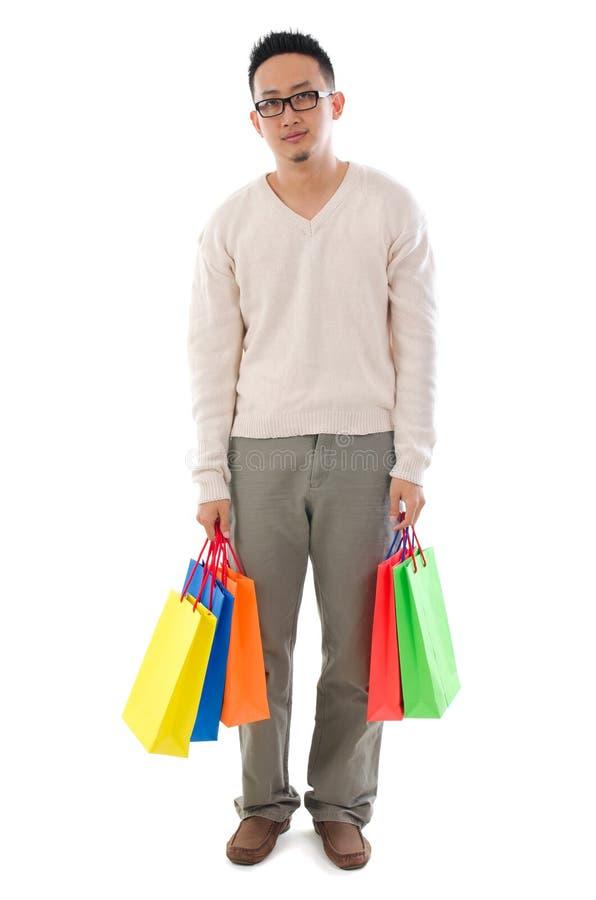 Пробуренный азиатский человек держа хозяйственные сумки стоковое фото rf
