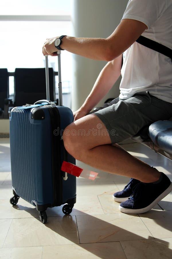 Пробуренный пассажир ждать его полет на авиапорте стоковые фотографии rf