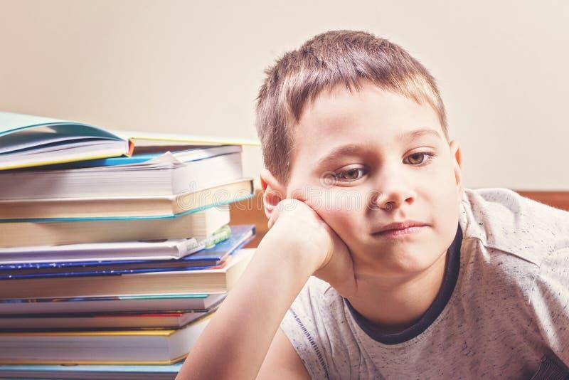 Пробуренный ребенок между кучами книг стоковые изображения