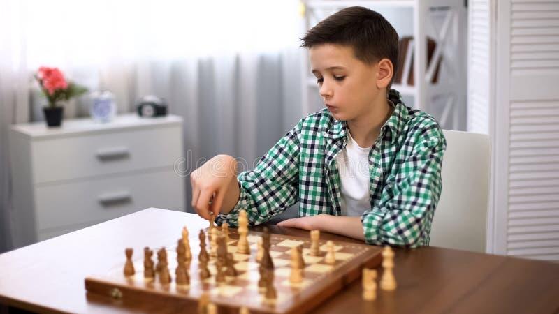 Пробуренный школьник играя шахматы, недостаток друзей, интеллектуальное хобби, отдых стоковое изображение rf