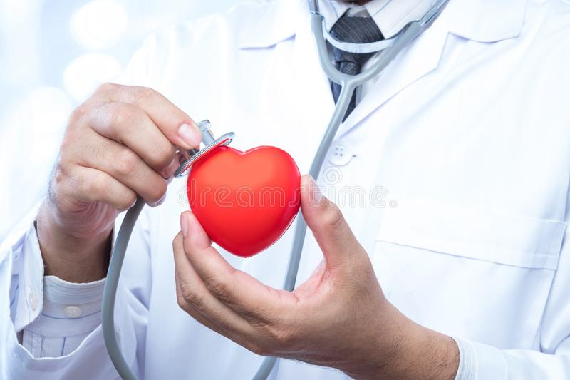 Проверите вверх на красном шарике сердца на офисе нерезкости в больнице и стоковое изображение