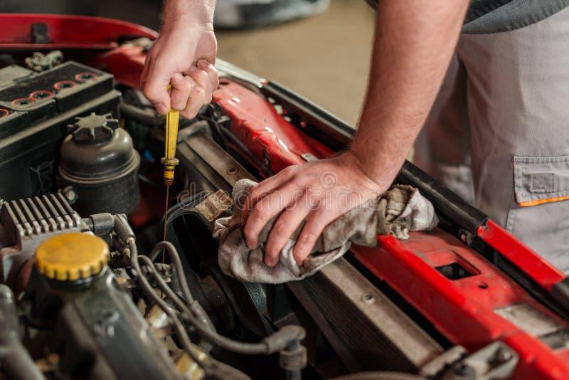 Проверять для масла двигателя на автомобиле стоковое изображение rf