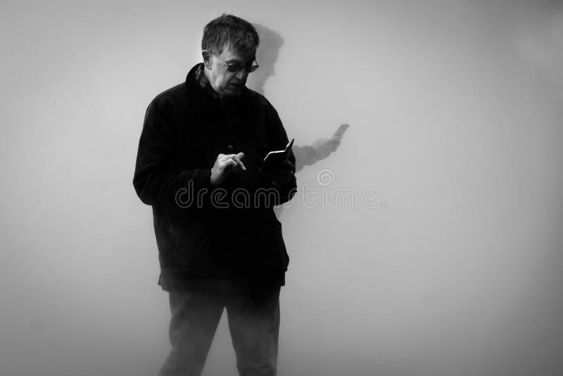 Проверяющ телефон - исчезающ в тумане стоковое фото