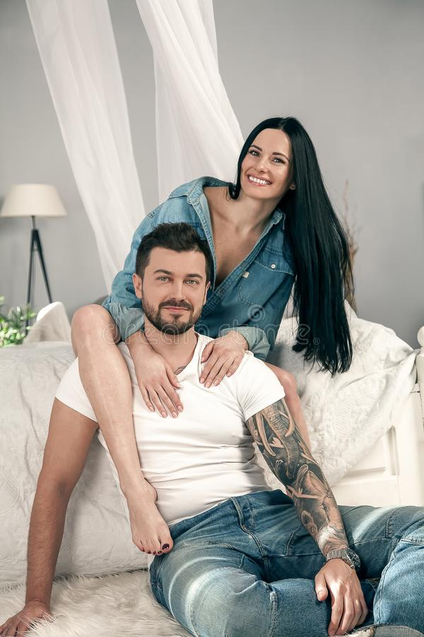 проветрите влюбленность Красивый молодой выпуск облигаций пар и усмехаться пока сидящ в спальне стоковое фото