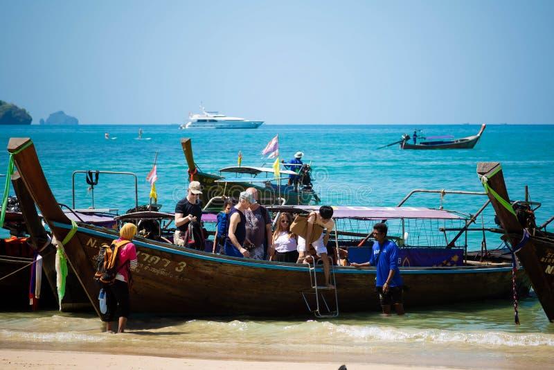 Провинция Krabi, пляж Railay, Таиланд - 18-ое февраля 2019: Туристы выходят шлюпки такси длинного хвоста Скачка в воду на стоковые фото