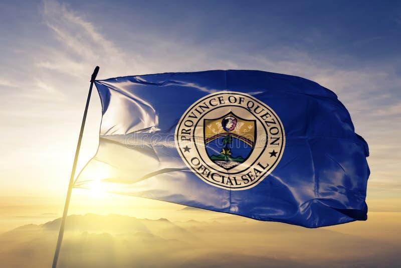 Провинция Quezon ткани ткани ткани флага Филиппин развевая на верхнем тумане тумана восхода солнца иллюстрация штока
