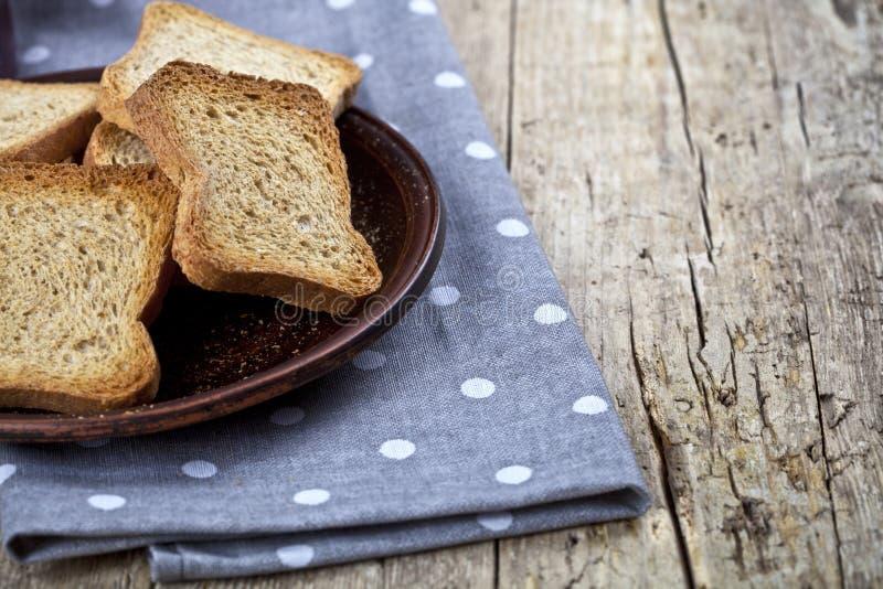 Провозглашанные тост куски хлеба хлопьев на коричневом керамическом крупном плане плиты на салфетке белья на деревенской предпосы стоковое фото