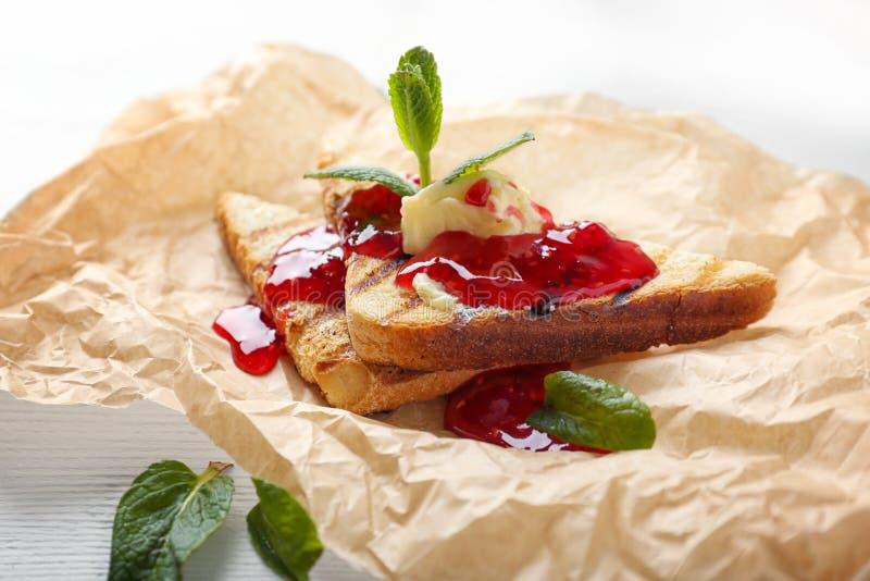 Провозглашанный тост хлеб со сладкими вареньем, маслом и мятой на пергаменте стоковое фото