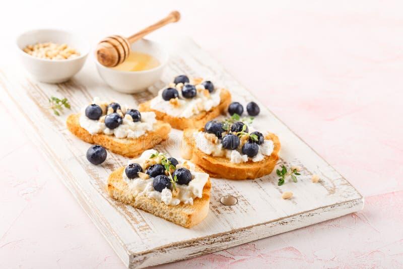 Провозглашать при свежие служат сыр, тимиан, мед и фундуки рикотты голубики ягод, который стоковые изображения rf