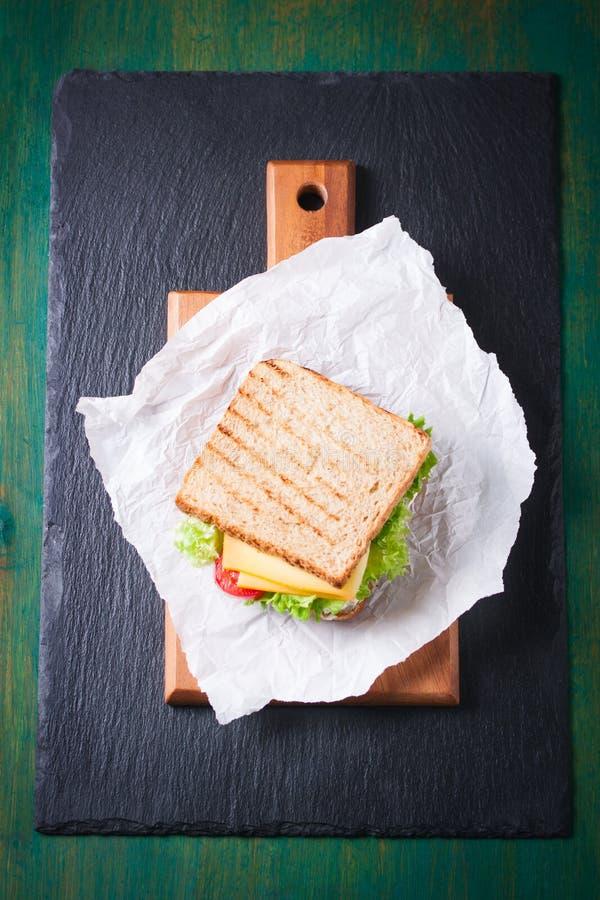 Провозглашанный тост сандвич с листьями, томатами и сыром салата с вилкой на разделочной доске на темной предпосылке стоковое изображение