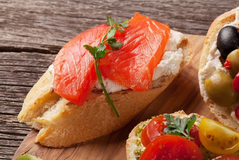 Провозглашать сандвичи с оливками, томатами, семгами стоковая фотография