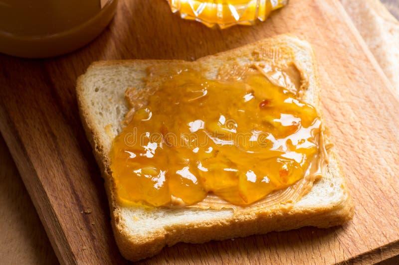 Провозглашать сандвич с арахисовым маслом и оранжевым вареньем стоковое изображение