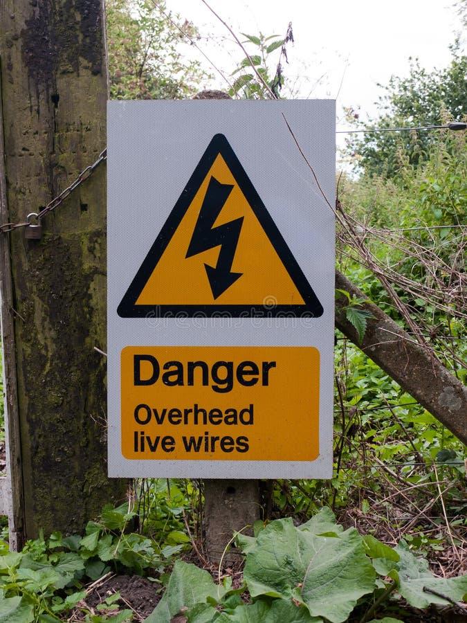 Провода под напряжением предупреждающей желтой опасности знака треугольника надземные стоковое изображение rf