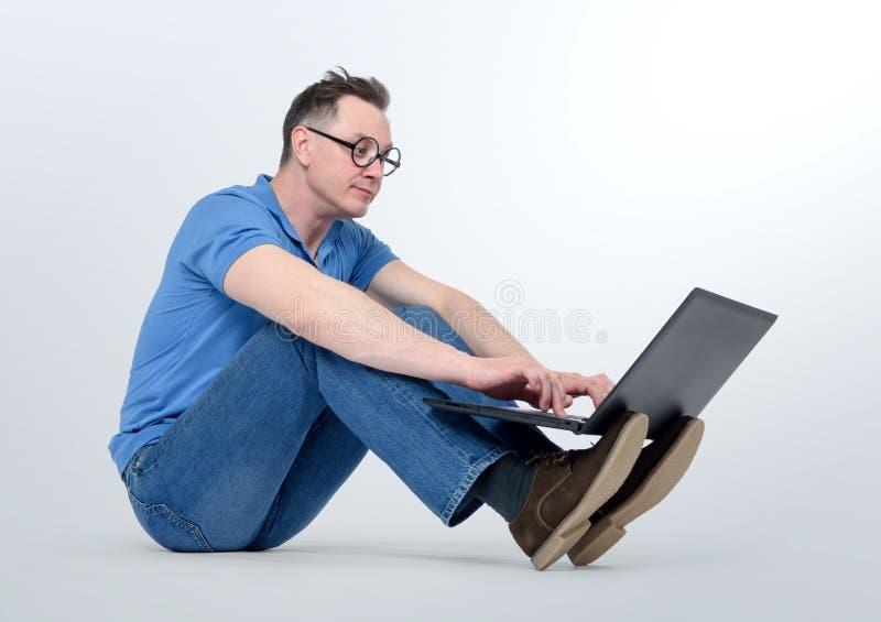 Программист в деятельности стекел на компьтер-книжке и усаживании на поле стоковое фото