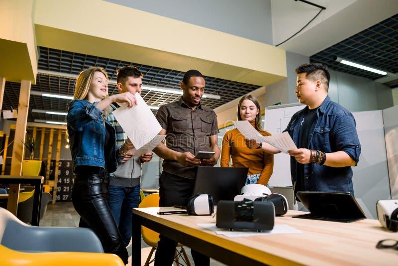 Программного обеспечения молодые люди испытывать программистов новые приложения со стеклами, ноутбуками и планшетами виртуальной  стоковые фото