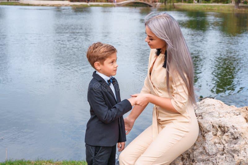 Прогулка матери и сына в парке озером стоковое изображение
