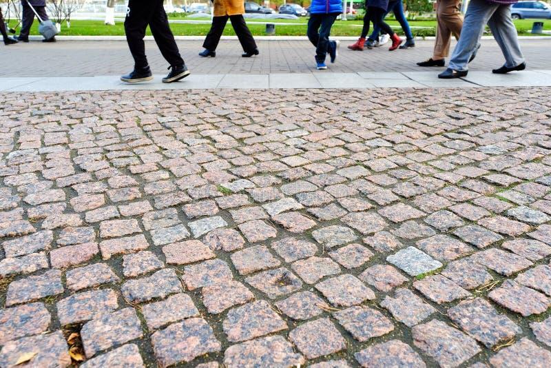 Прогулка пешеходов на тротуаре Старый гранит вымощая взгляд конца-вверх сверху тротуар стоковое фото