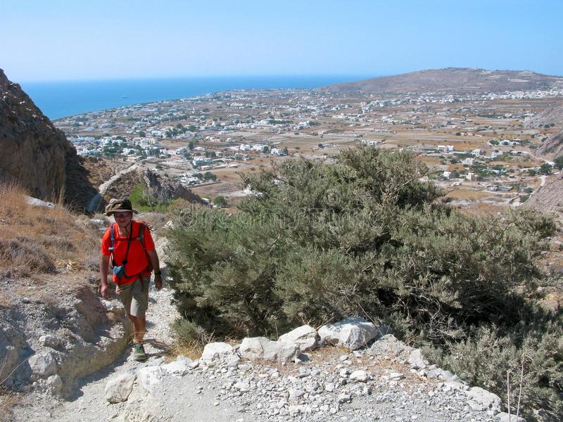 Прогулка человека улыбки вверх на пути горы santorini острова холма Греции зданий стоковая фотография