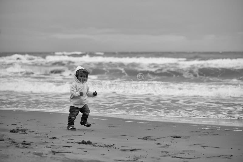 Прогулка ` s детей на пляже Радостный мальчик бежать на пляже стоковое фото