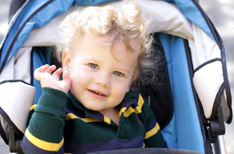 прогулочная коляска ребенка счастливая стоковое изображение