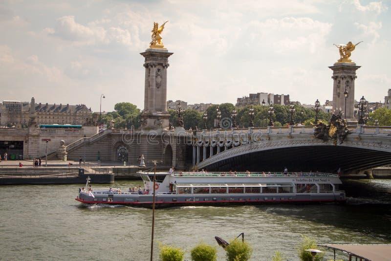 Прогулочный катер с туристами плавая под Александром третий мост в Париже стоковые фото
