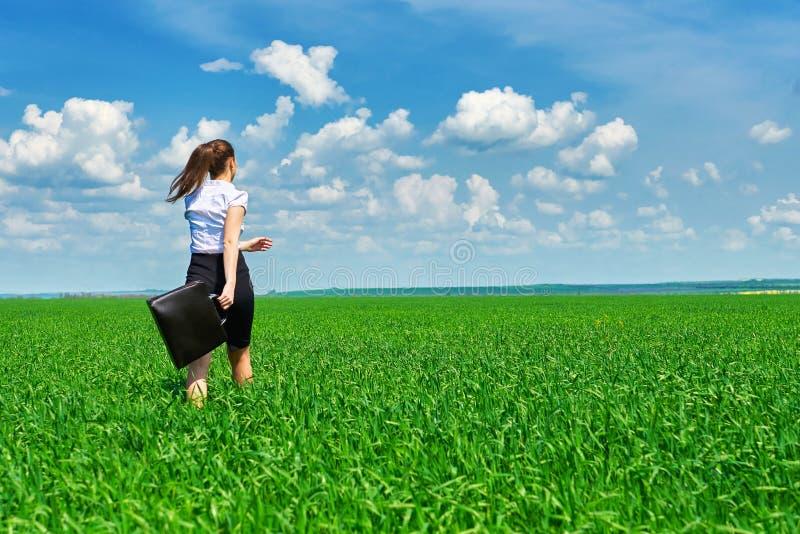 Прогулка бизнес-леди на поле зеленой травы внешнем и ослабляет под солнцем Красивая маленькая девочка одела в костюме отдыхая, la стоковая фотография