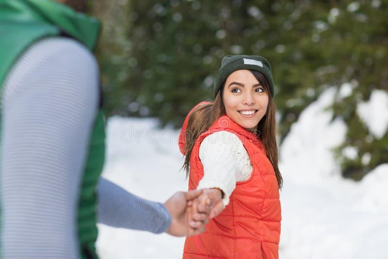 Прогулка зимы молодого азиатского леса снега пар руки человека владением женщины романтичного внешняя стоковая фотография rf