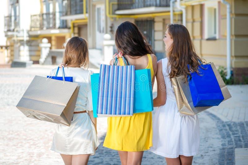 Прогулка подруг к магазину 3 девушки держа хозяйственные сумки стоковые изображения rf