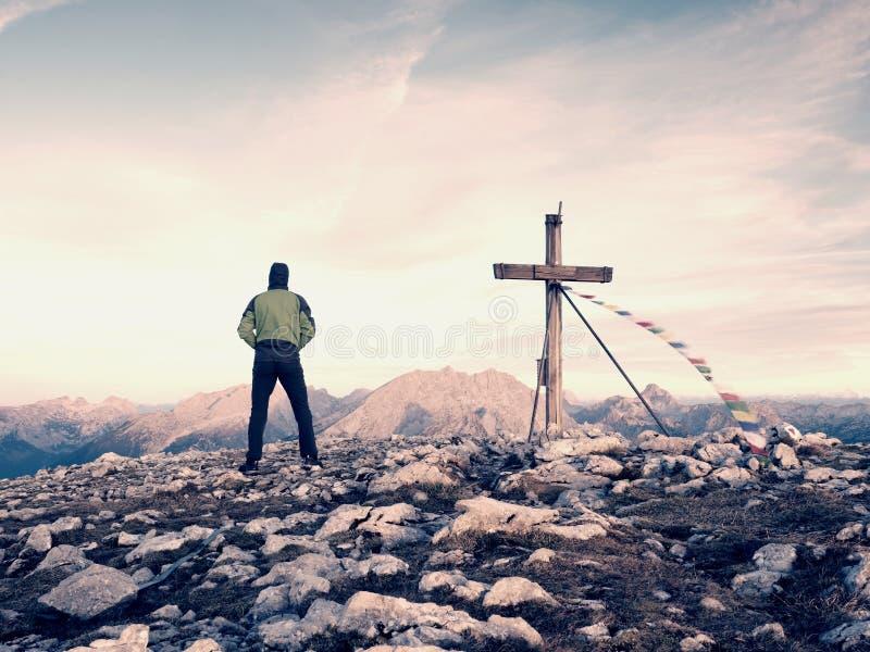 Прогулка человека туристская к кресту на горном пике Выравнивать темное, красочное небо во время захода солнца стоковое фото rf