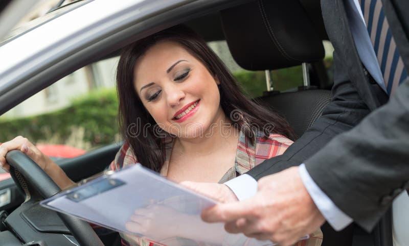 Продавец автомобилей давая объяснения на доске сзажимом для бумаги к молодой женщине стоковое изображение