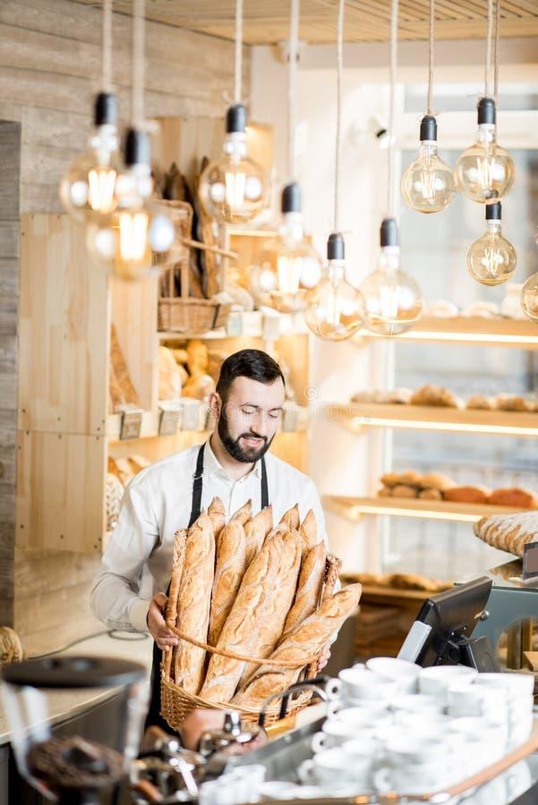 Продавец в магазине хлеба стоковое фото