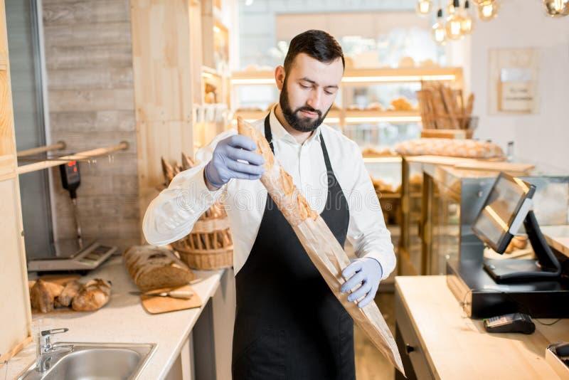 Продавец в магазине хлеба стоковые изображения rf