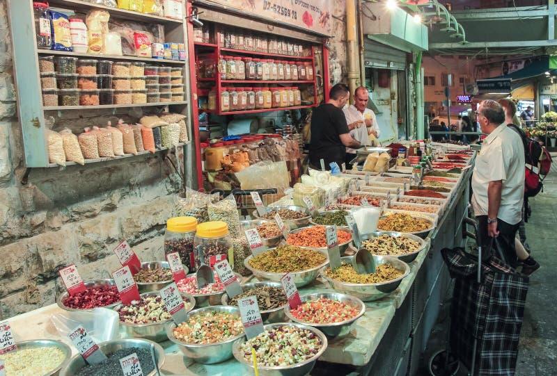 Продавец в открытом магазине весит покупателя специи в рынке Mahane Yehuda в Иерусалиме, Израиле стоковое фото rf