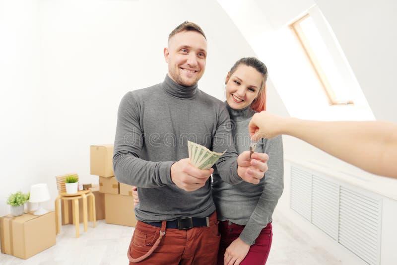 Продавец дает клиентам ключи новой квартире стоковое изображение rf