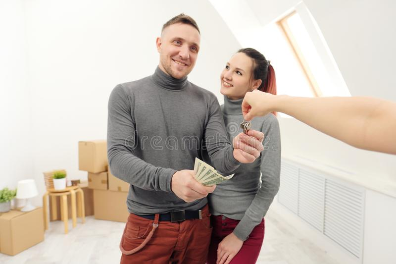 Продавец дает клиентам ключи новой квартире стоковое изображение