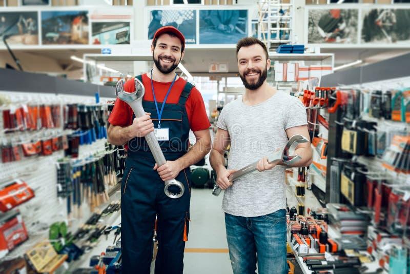 Продавец и бородатый клиент представляя с ключами гиганта в магазине електричюеских инструментов стоковые изображения rf