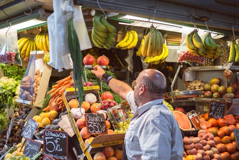 Продавец на свежей фруктовой лавке на рынке стоковое фото