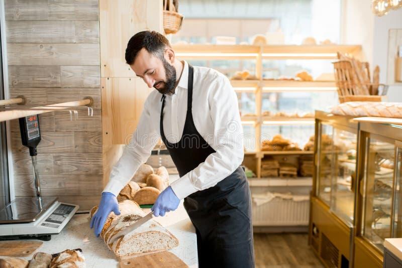 Продавец режа хлеб стоковая фотография