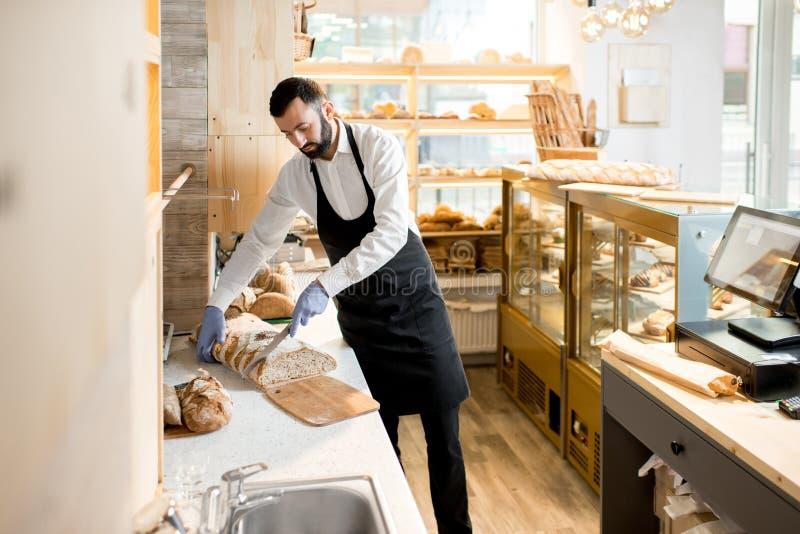 Продавец режа хлеб стоковые изображения