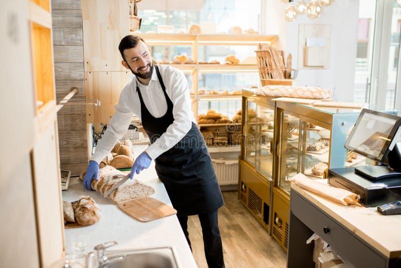 Продавец режа хлеб стоковая фотография rf