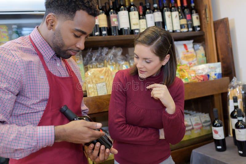 Продавец советуя клиенту на итальянском вине стоковое изображение rf