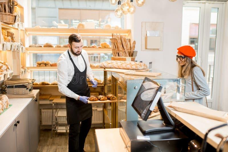Продавец с клиентом в магазине хлебопекарни стоковые фото