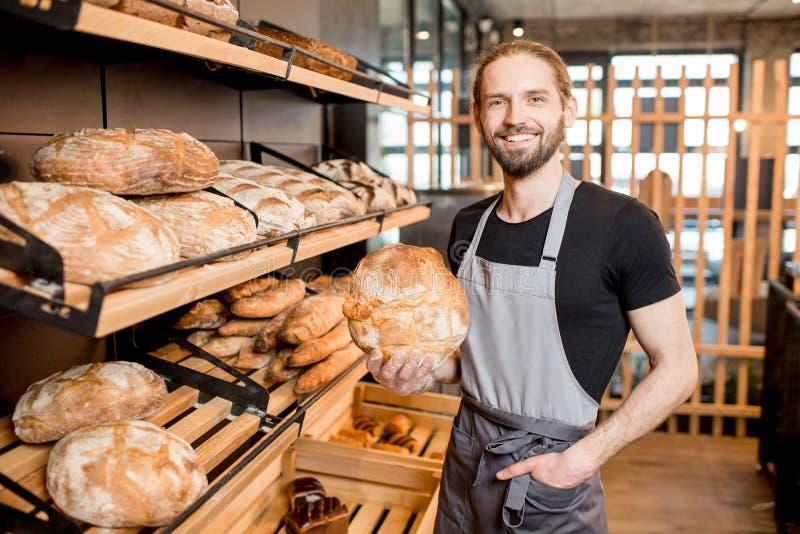Продавец хлеба на магазине хлебопекарни стоковая фотография
