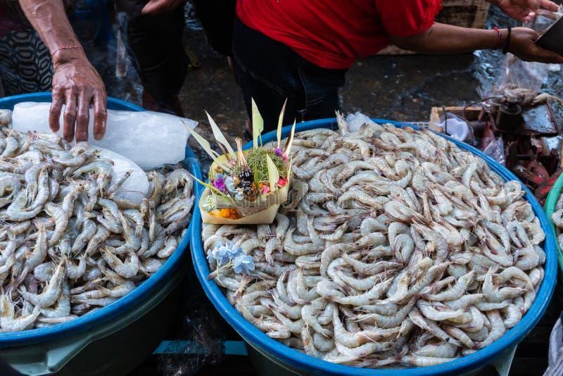 Продавцы креветки в традиционных рынках Badung продали креветку на подносе который ранее был послужен canang как благословение стоковое изображение